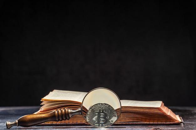 Bitcoin neben dem buch durch die lupe sichtbar. kryptowährungs-wissenskonzept.