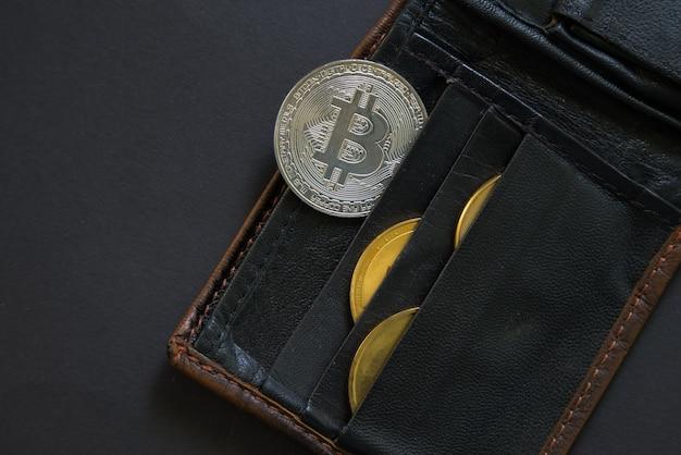 Bitcoin ragt aus einer brieftasche o schwarz