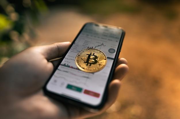 Bitcoin und charts im smartphone in der hand abendlicht