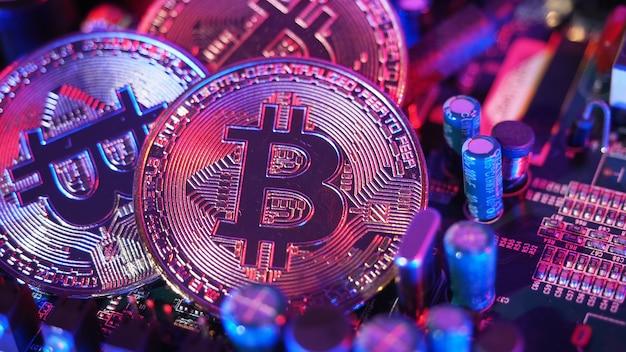 Bitcoin und halbleiter. stellen sie den bergbau in cryptocurrency dar, der die globale erwärmung verursacht. bitcoins auf cpu-platine. nahaufnahme bitcoin mit blauem und rosa licht. platine mit münze. online-asset-konzept.