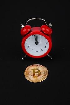 Bitcoin und roter wecker auf schwarzem hintergrund. kryptowährungskonzept. goldfarbene münze.