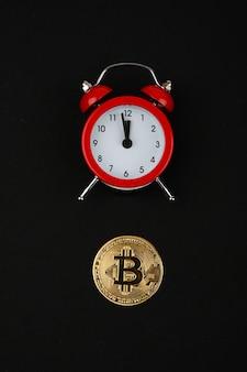 Bitcoin und roter wecker auf schwarzem raum. kryptowährungskonzept. goldfarbene münze.