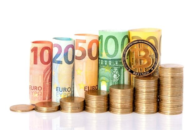 Bitcoin und zehn, zwanzig, fünfzig, einhundert, zweihundert und münzen euro rollten banknoten auf weiß