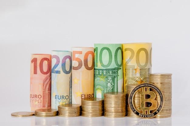 Bitcoin und zehn, zwanzig, fünfzig, einhundert, zweihundert und münzen euro rollten banknoten