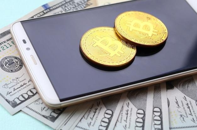 Bitcoins liegt auf einem smartphone und hundert dollarscheinen auf einem hellblauen hintergrund