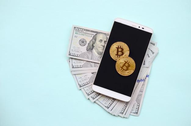 Bitcoins liegt auf einem smartphone und hundert dollarscheinen