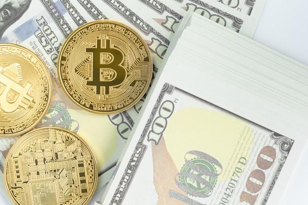 Bitcoins münze und us-banknoten von einhundert dollar. nahaufnahme von metallglänzenden bitcoin-kryptowährungsmünzen und us-dollar