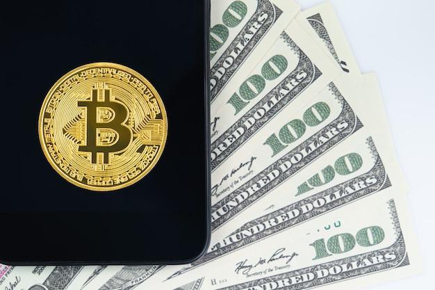 Bitcoins münze und us-banknoten von hundert dollar mit smartphone. nahaufnahme von metallglänzenden bitcoin-kryptowährungsmünzen und us-dollar