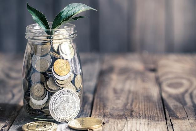 Bitcoins und glas mit münzen