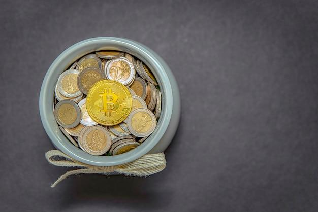 Bitcoins und münzen in einem glas auf grauem hintergrund isoliert