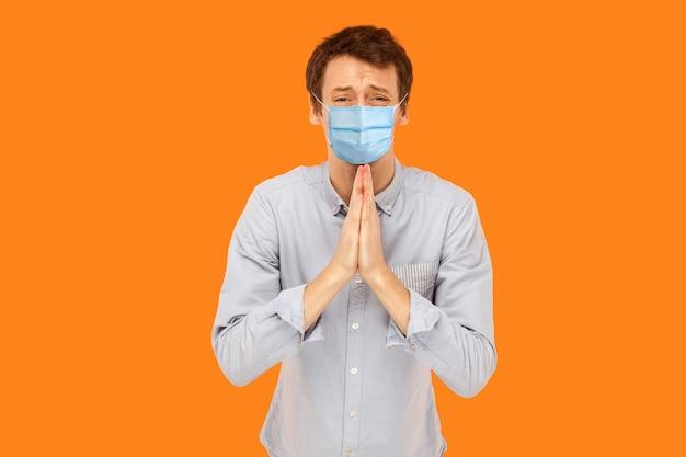 Bitte hilf mir. portrait von traurigen sorgen junger arbeiter mit medizinischer maske, die mit palmhänden steht, sich sorgen macht und die kamera bettelt oder bittet. indoor-studioaufnahme auf orangem hintergrund isoliert.
