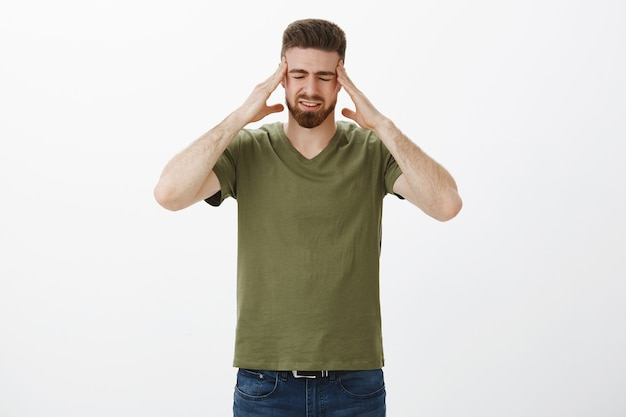 Bitte hör auf, meinen kopf auszublasen. das porträt eines unbehaglichen gutaussehenden bärtigen mannes, der kopf und schläfen berührt, schließt die augen vor dem schmerzhaften gefühl der migräne