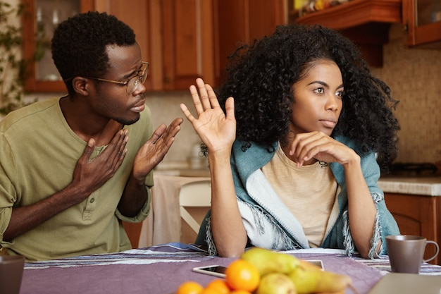 Bitte verzeih mir. unglücklicher afroamerikanischer männlicher betrüger, der hand auf seiner brust hält und sich bei der schönen gleichgültigen frau entschuldigt, die alle seine ausreden ignoriert und ablehnt und ihm sagt, er solle sich verlaufen