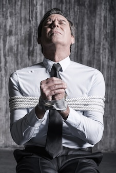 Bitten um hilfe. schockierter gefesselter geschäftsmann, der um hilfe bettelt, während er die augen geschlossen hält und am stuhl mit schmutziger wand im hintergrund sitzt