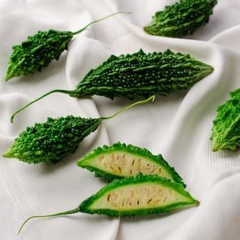 Bittere gurke oder momordica auf weißem textilhintergrund. exotische küche. flaches, quadratisches bild