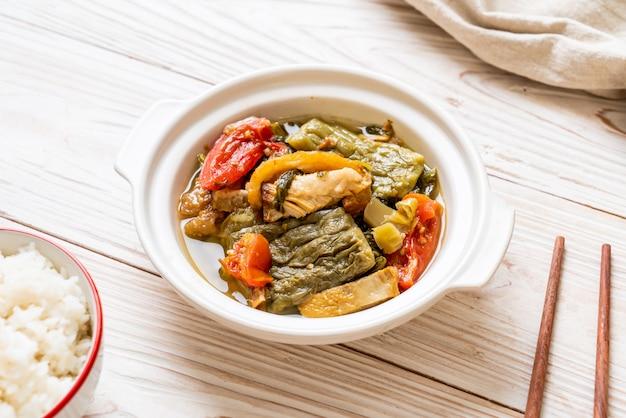 Bitterer kürbis und konservierte senfgrüne suppe mit schweinefleisch