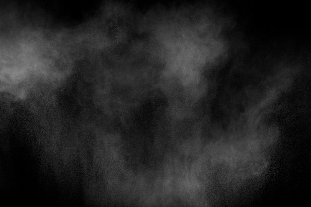 Bizarre formen der explosionwolke des weißen pulvers gegen schwarzen hintergrund. weiße staubpartikel spritzen.