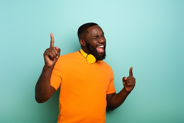 Black boy mit gelbem headset hört musik und tänze