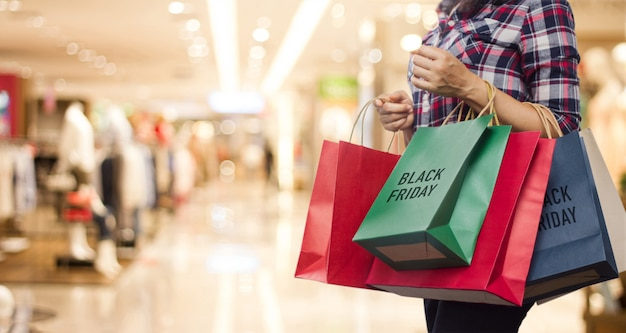 Black friday, frau, die viele einkaufstaschen beim gehen in das einkaufszentrum hält