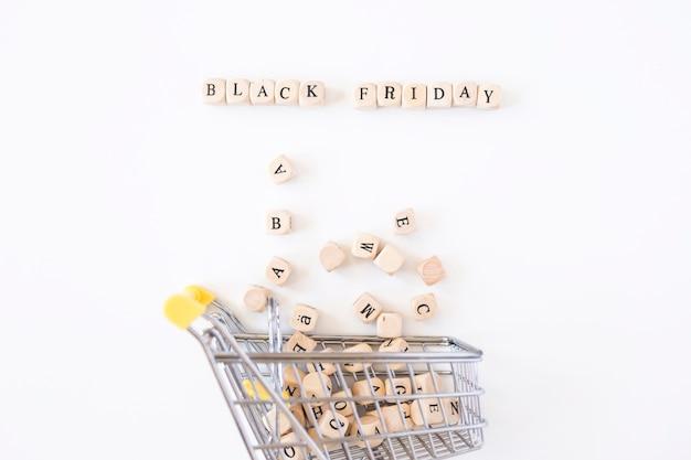 Black friday-inschrift auf würfeln mit kleinem einkaufswagen