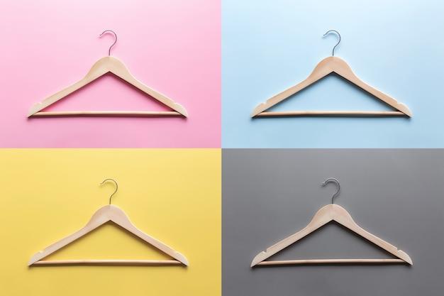 Black friday- oder bekleidungsindustrie-konzeptcollage auf mehrfarbigem buntem hintergrund flach mit hölzernen kleiderbügeln