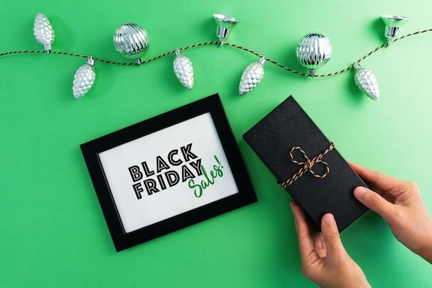 Black friday sale auf rahmen mit geschenkbox und girlandenlichtern