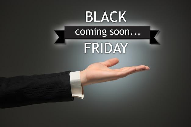 Black friday sale - weihnachtseinkaufskonzept - text und männliche hand auf schwarz