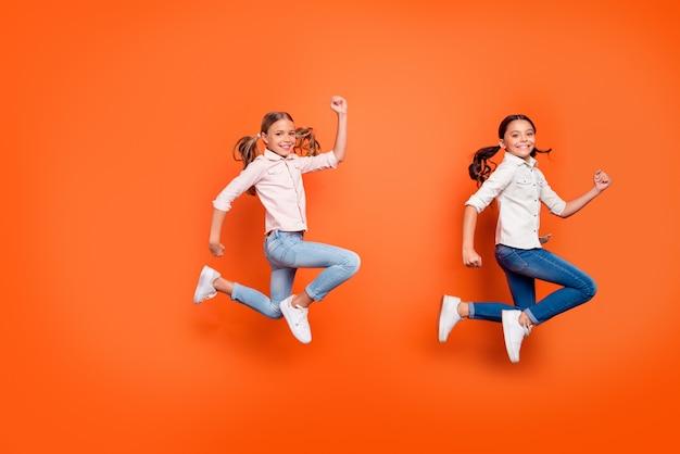 Black friday schnäppchen! profilfoto in voller länge von positiv funky zwei kinder springen rennen eile für herbstrabatte tragen freizeitkleidung isoliert orange farbe hintergrund