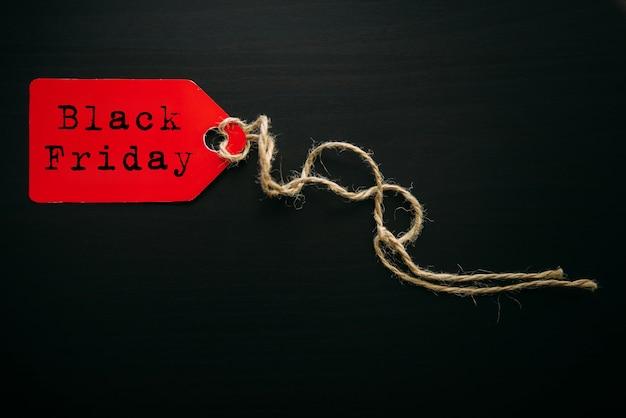 Black friday shopping sale konzept. text auf rotem etikett auf schwarzem hölzernem hintergrund im sonnenlicht.