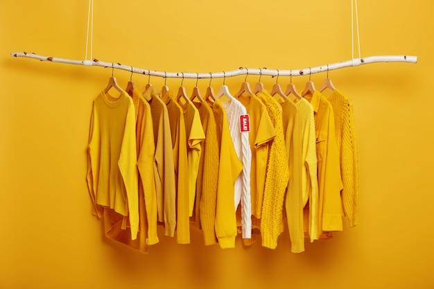 Black friday, shopping und großes verkaufskonzept. detailbild der gelben kleidung und des weißen pullovers mit dem etikettenanhänger, der auf gestell im bekleidungsgeschäft hängt.