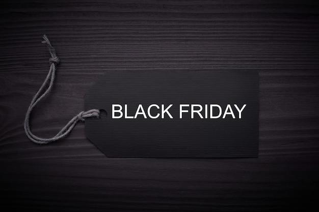 Black friday-text auf einem schwarzen tag auf schwarzem papierhintergrund