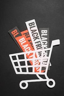 Black friday-verkäufe auf papierblättern im einkaufswagen