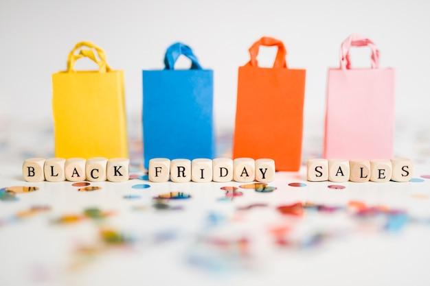Black friday-verkaufsaufschrift auf würfeln mit bunten einkaufstaschen