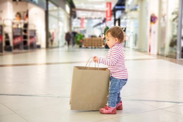 Black friday-verkaufskonzept, einkaufen mit kindern, naturfreundliches einkaufen. kleines süßes baby nimmt große bastelpapiertüte zum einkaufen mit exemplar auf. nahaufnahme, weichzeichner, im hintergrund sho