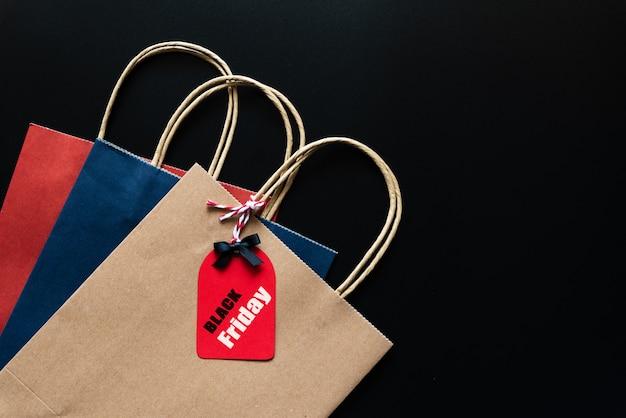 Black friday-verkaufstext auf einem roten tag mit einkaufstasche auf schwarzem hintergrund. online einkaufen