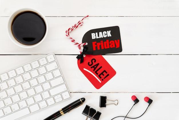 Black friday-verkaufstext auf tag mit tastatur und kaffee