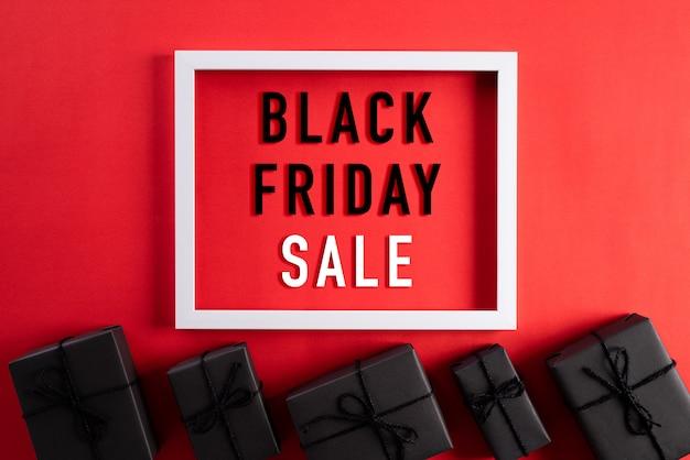 Black friday-verkaufstext auf weißem bilderrahmen mit schwarzer geschenkbox