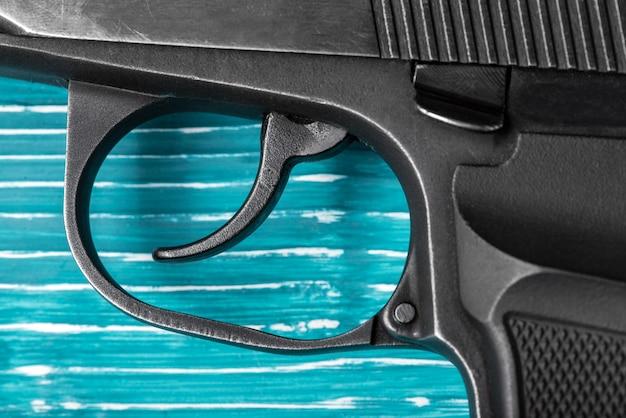 Black gun auf einer blauen hölzernen oberfläche close-up. studioaufnahme draufsicht