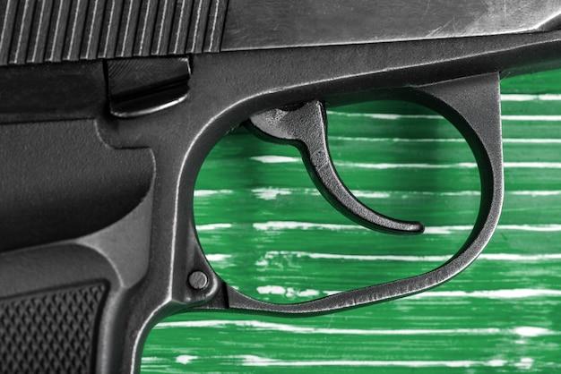 Black gun auf einer grünen hölzernen oberfläche close-up. studioaufnahme draufsicht