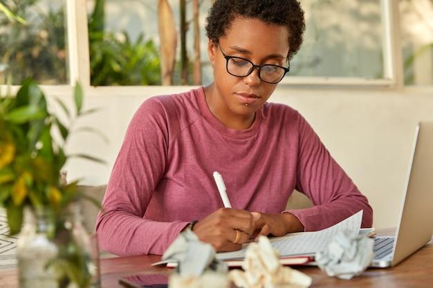 Black lady creats publikation, schreibt aufzeichnungen in notizblock, konzentriert sich auf das schreiben, verwendet laptop-computer für die suche nach informationen im internet, sitzt am arbeitsplatz mit zerknitterten papier creats testprüfung