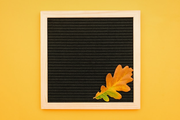Black letter board und herbsteichenblatt auf gelbem grund.