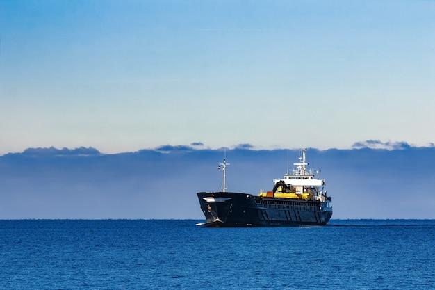 Black sailing bulk carrier. frachtschiff mit bagger mit großer reichweite, der sich im stillen wasser am sonnigen tag durch das meer bewegt