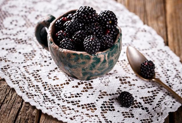 Blackberry fresh in einer tasse in der nähe eines löffels