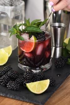 Blackberry-sommer-mojito-cocktail. kaltes erfrischendes alkoholisches bio-getränk mit beeren, limette, minze