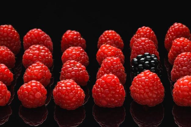 Blackberry und himbeere auf einem schwarzen tisch, unterscheiden sich von anderen