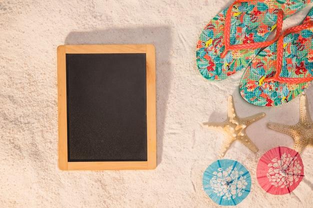 Blackboard flip flops seesterne und sonnenschirme auf sand