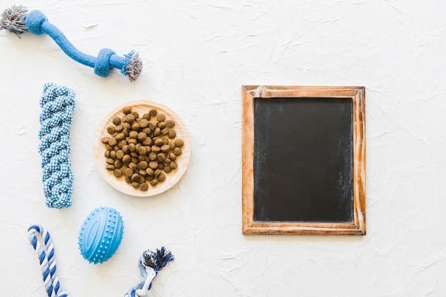 Blackboard in der nähe von hund spielzeug und essen