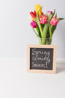 Blackboard in der nähe von vase mit tulpen