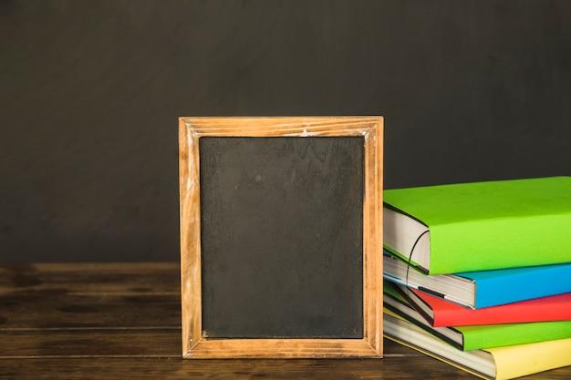 Blackboard mit büchern auf dem tisch