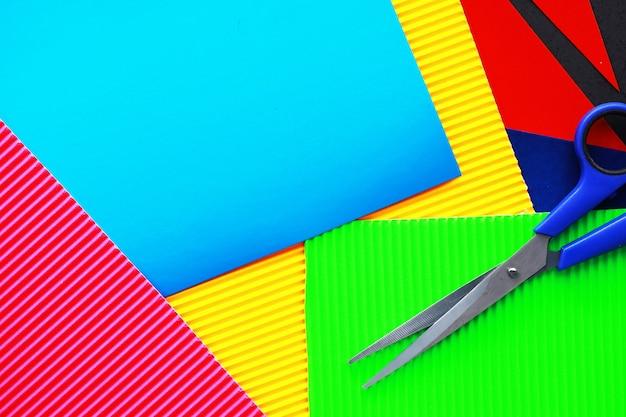 Blätter aus farbigem papier, schillernde palette aus farbigem papier, regenbogenfarben. draufsicht auf den tisch mit farbigem papier und schere.